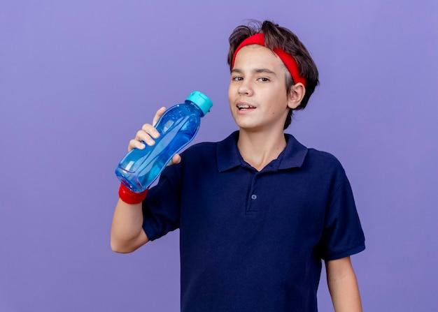 Giovane ragazzo sportivo bello che indossa la fascia e braccialetti con bretelle dentali che tiene la bottiglia di acqua che guarda l'obbiettivo che si prepara a bere acqua isolato su sfondo viola con spazio di copia