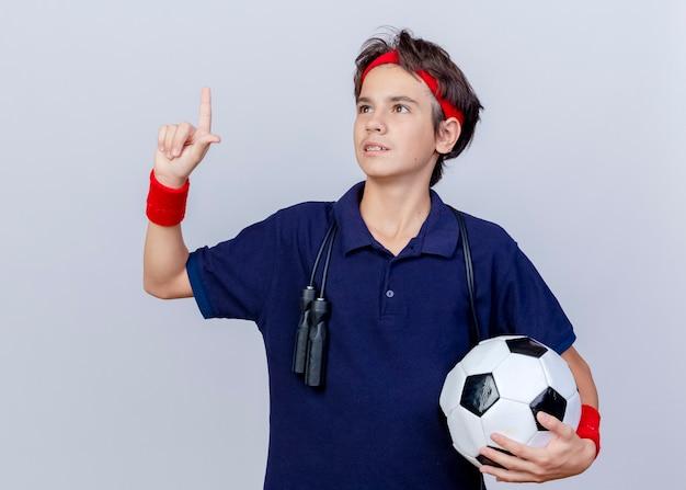 Giovane ragazzo sportivo bello che indossa la fascia e braccialetti con bretelle dentali e corda per saltare intorno al collo tenendo il pallone da calcio guardando in alto facendo gesto perdente isolato su priorità bassa bianca