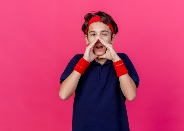 Young handsome sporty boy wearing headband and wristbands with dental braces looking at camera keeping hands around mouth calling out to someone isolated on crimson background with copy space
