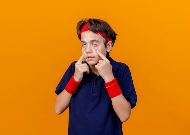 Young handsome sporty boy wearing headband and wristbands with dental braces pulling down eye lids isolated on orange wall