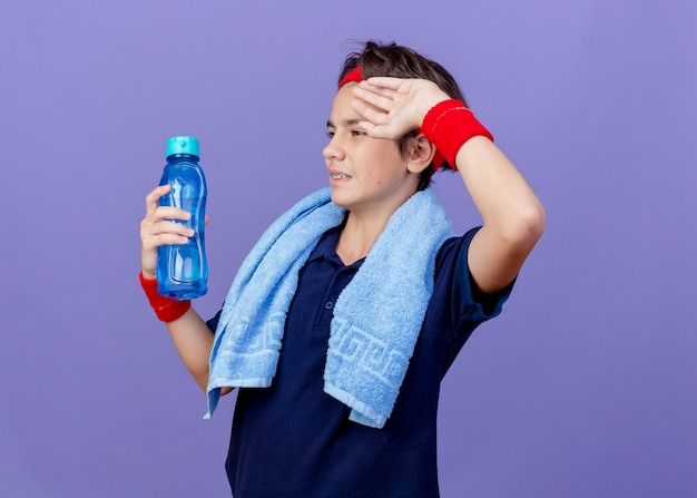 Young handsome sporty boy wearing headband and wristbands with dental braces and towel around neck isolated on purple wall