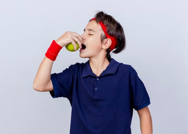 Bel giovane ragazzo sportivo che indossa la fascia e braccialetti con bretelle dentali girando la testa a lato mordere la mela con gli occhi chiusi isolati su sfondo bianco