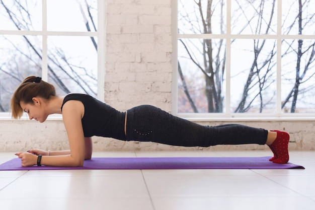 Young handsome sporty girl standing on plank pose during yoga exercise