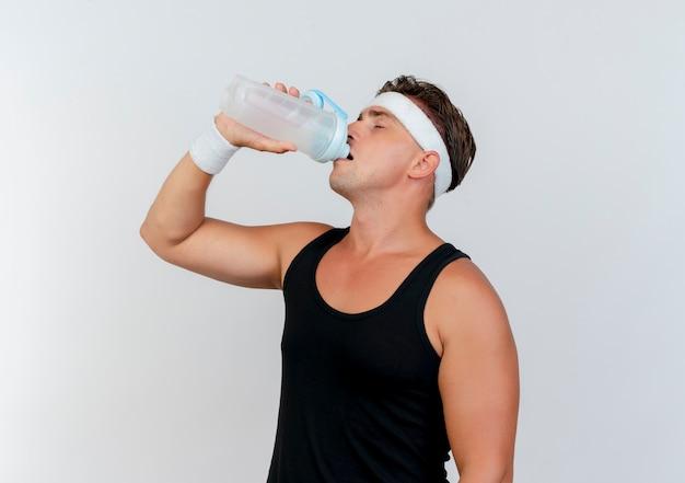 コピースペースと白い背景で隔離の目を閉じて水筒から水を飲むヘッドバンドとリストバンドを身に着けている若いハンサムなスポーティな男 無料写真