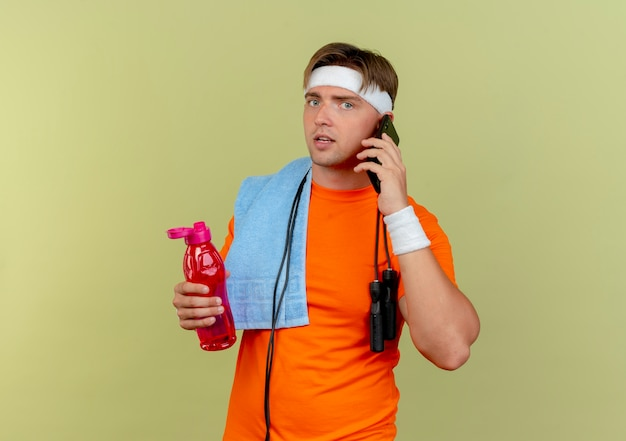 ヘッドバンドとリストバンドを身に着けている若いハンサムなスポーティな男は、首に縄跳びと肩にタオルを持って水筒を保持し、コピースペースでオリーブグリーンの背景に分離された電話で話している