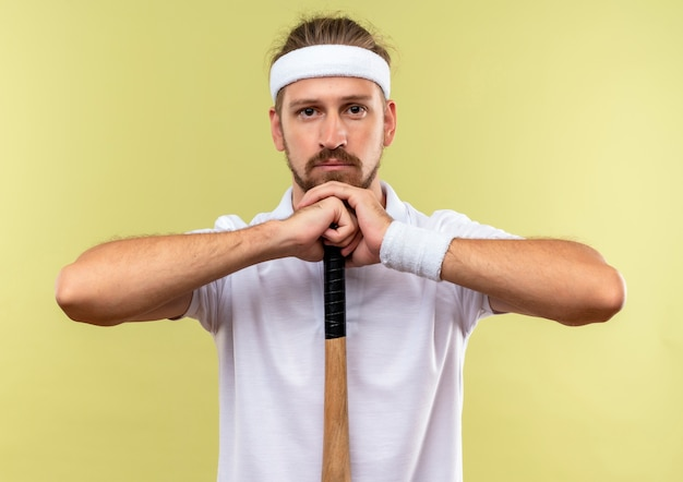 Young handsome sporty man wearing headband and wristbands holding baseball bat and putting head on hands looking  isolated on green space
