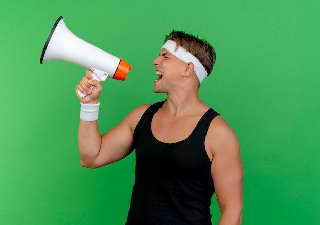 Young handsome sporty man wearing headband and wristbands shouting in loud speaker isolated on green background with copy space