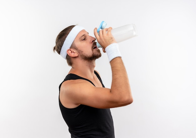Young handsome sporty man wearing headband and wristbands standing in profile view and drinking water from bottle isolated on white space