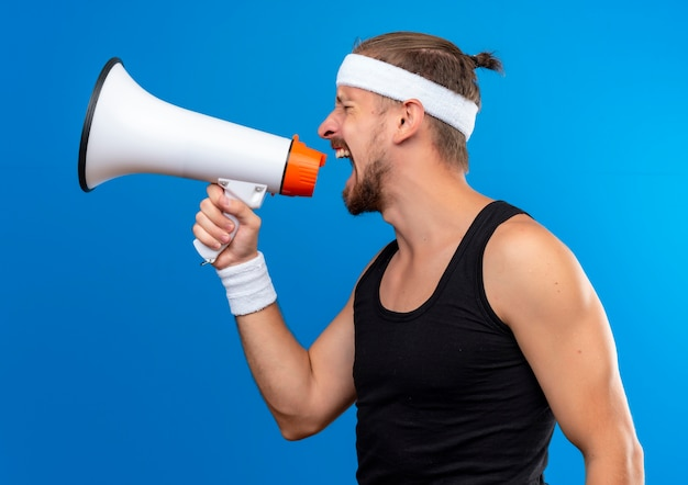 Young handsome sporty man wearing headband and wristbands standing in profile view and shouting in loud speaker at side isolated on blue space