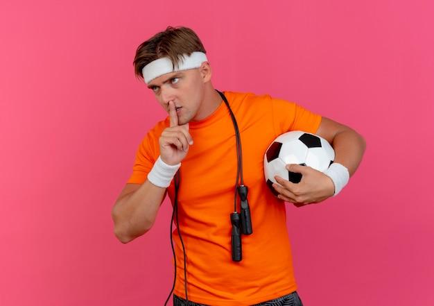 Giovane uomo sportivo bello che indossa la fascia e braccialetti con la corda per saltare intorno al collo tenendo il pallone da calcio guardando il lato e gesticolando silenzio isolato su sfondo rosa con spazio di copia
