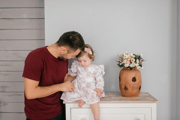 明るい部屋で若いハンサムな強いお父さんは彼のかわいい小さな娘を保持します