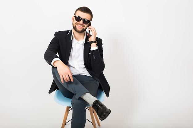 Giovane uomo bello alla moda hipster in giacca nera, stile di affari, camicia bianca, isolato, seduto rilassato sulla sedia da ufficio, parlando sullo smartphone, sorridente, felice, positivo, occhiali da sole