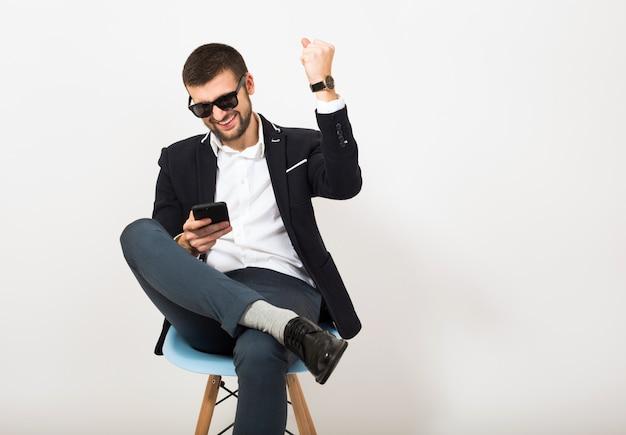 Giovane uomo bello alla moda hipster in giacca nera, stile di affari, camicia bianca, isolato, seduto rilassato sulla sedia da ufficio, utilizza lo smartphone, sorridente, felice, positivo, occhiali da sole, gesto, emotivo