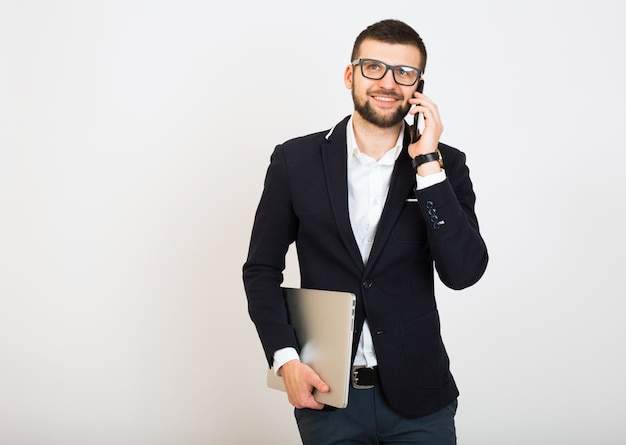 Young handsome stylish hipster man in black jacket, business style, white shirt, isolated, white background, smiling, attractive, looking confident, holding laptop, talking on smartphone