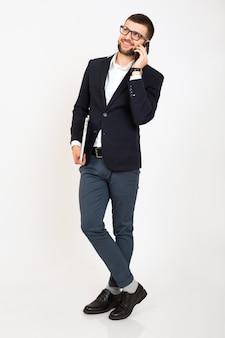 Giovane uomo bello alla moda hipster in giacca nera, stile di affari, camicia bianca, isolato, sfondo bianco, sorridente, in piedi a tutta altezza, guardando fiducioso, tenendo il laptop, parlando sullo smartphone