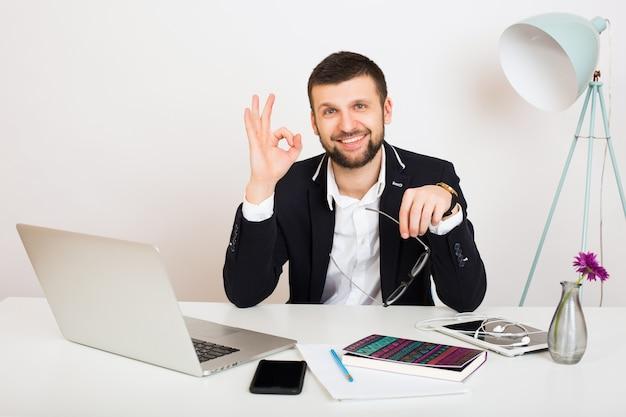 オフィスのテーブル、ビジネススタイル、白いシャツ、分離、ラップトップに取り組んで黒いジャケットの若いハンサムなスタイリッシュな流行に敏感な男、起動、職場、笑顔、幸せ、肯定的、