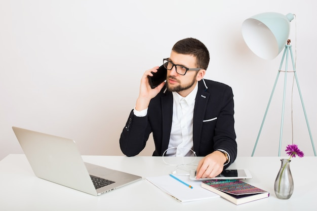 オフィスのテーブルに座っている黒いジャケットの若いハンサムなスタイリッシュな流行に敏感な男、ビジネススタイル、白いシャツ、分離、作業、ラップトップ、起動、職場、スマートフォンで話している、笑顔、肯定的