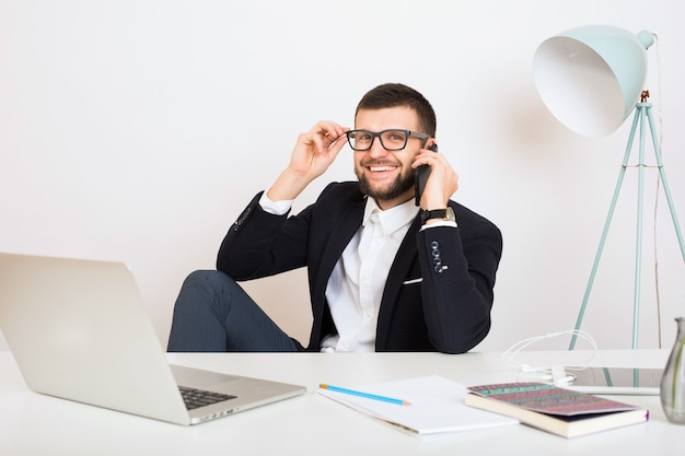 Молодой красивый стильный битник мужчина в молодой куртке, сидя за офисным столом