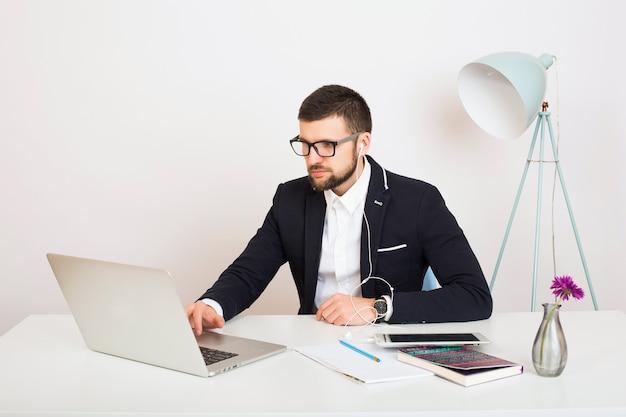 사무실 테이블에서 일하는 젊은 재킷을 입은 젊고 세련된 힙스터 남자
