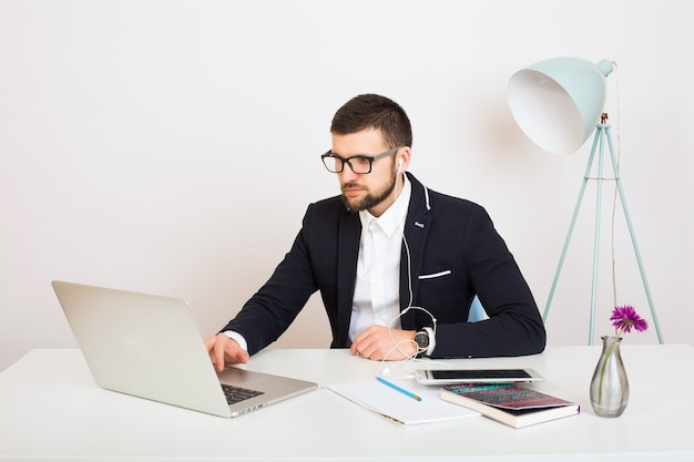 Young handsome stylish hipster man in young jacket working at office table