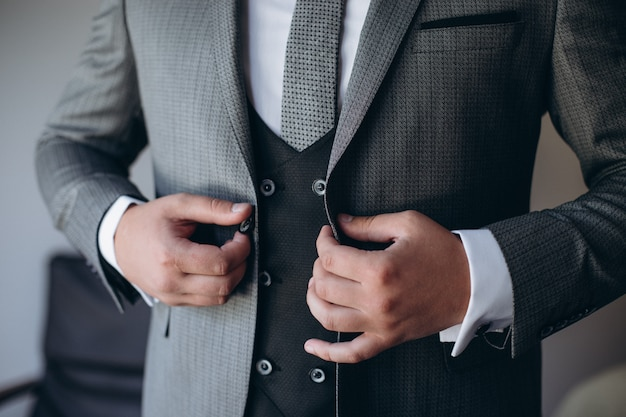 Young handsome stylish man dressed in modern formal clothes buttoning jacket. close up of hands of guy in gray jacket, violet shirt. person ready for wedding celebration or graduation.