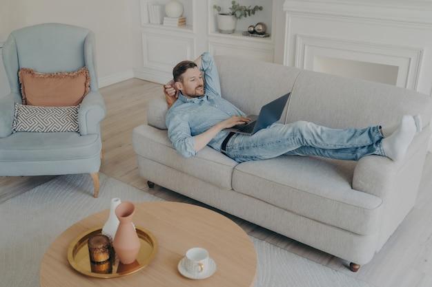 Молодой красивый успешный бизнесмен, работающий удаленно дома, собирая данные со своим ноутбуком, лежа на диване с головой, положив руку на руку в легкой гостиной