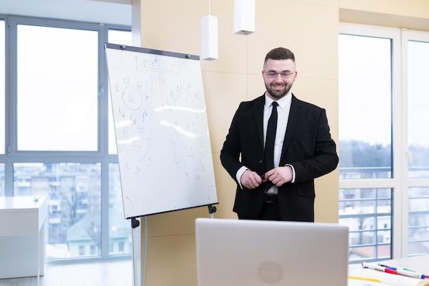 안경과 양복에 젊은 잘 생긴 성공적인 남자는 사무실과 집에서 온라인으로 회의 훈련을 보유