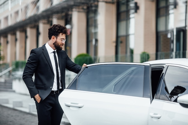 Young handsome successful manager in black suit entering the rear seat of his car near a modern business center, on the street of big city