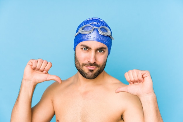 Young handsome swimmer man isolated feels proud and self confident, example to follow.