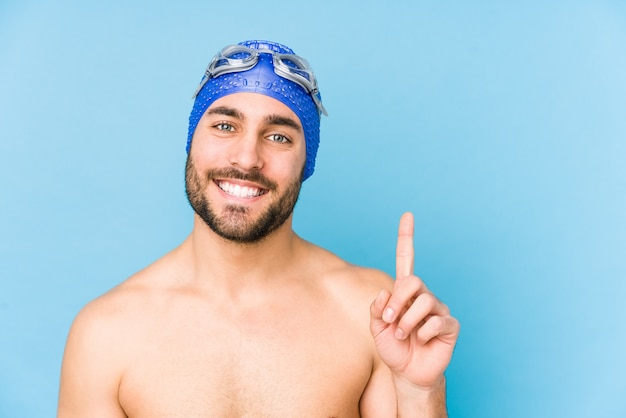 Young handsome swimmer man isolated showing number one with finger.