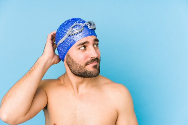Young handsome swimmer man isolated touching back of head, thinking and making a choice.