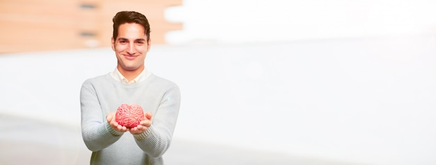 Young handsome tanned man with a brain model