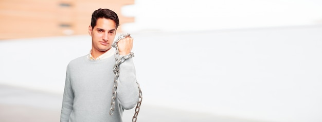 Young handsome tanned man with a chain. freedom concept