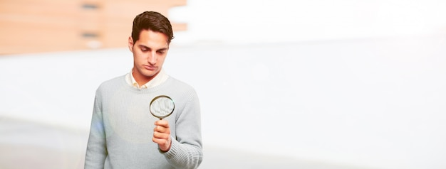 Young handsome tanned man with a magnifying glass