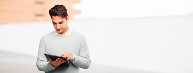Young handsome tanned man with a touch screen tablet