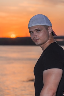 A young handsome tanned sports man in a cap stands on a sunset