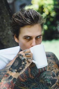 Young handsome tattooed man having breakfast in bed in the open air outdoors in the garden