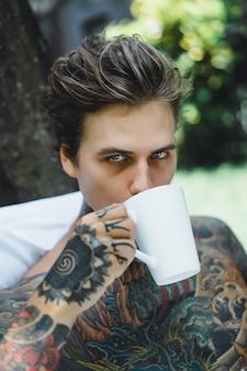 Молодой красивый татуированный человек, завтрак в постели на открытом воздухе на открытом воздухе в саду