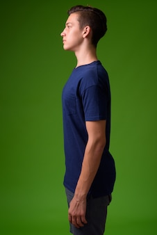 Young handsome teenage boy against green background