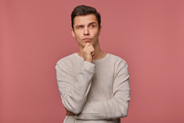 Giovane ragazzo pensante bello indossa in camicia a scacchi, guarda e tocca il mento lontano, pensa a un'auto nuova, isolata su sfondo rosa.