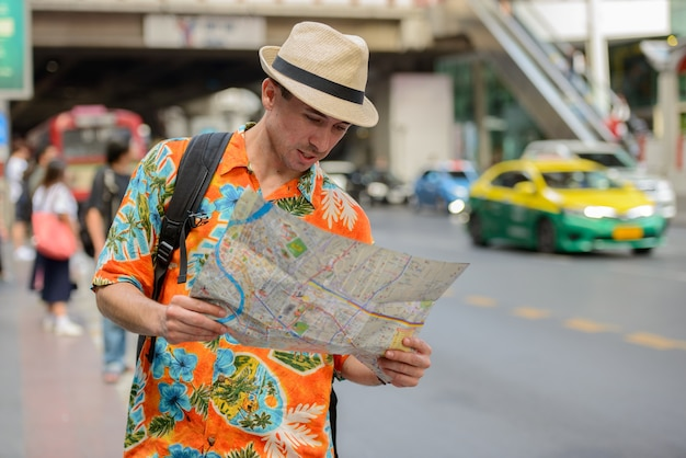 Молодой красивый туристический человек с рюкзаком читает карту на улицах города