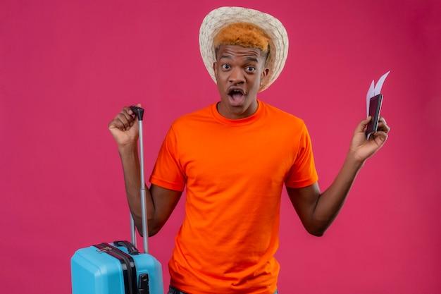 Молодой красивый мальчик-путешественник в летней шляпе, одетый в оранжевую футболку, держит дорожный чемодан и билеты на самолет