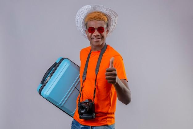 Молодой красивый мальчик-путешественник в летней шляпе, одетый в оранжевую футболку, держит дорожный чемодан, улыбаясь дружелюбно показывает палец вверх, стоя над белой стеной