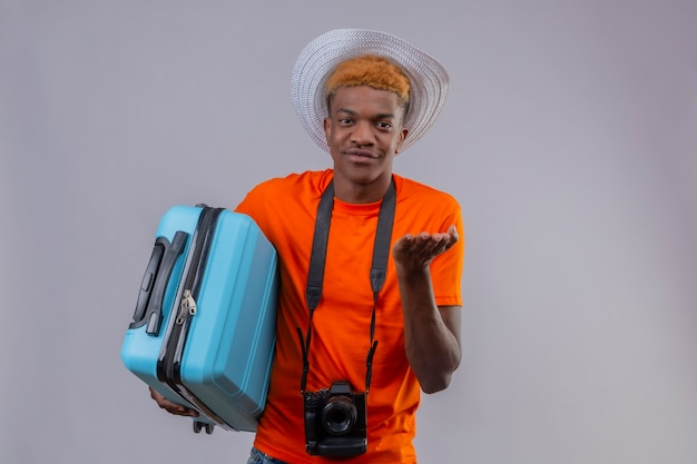 Young handsome traveler boy in summer hat wearing orange t-shirt with camera holding travel suitcase