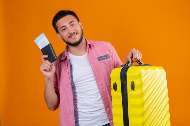 Молодой красивый путешественник, держащий авиабилеты и чемодан, смотрит в камеру с уверенной улыбкой, позитивным и счастливым положением на оранжевом фоне
