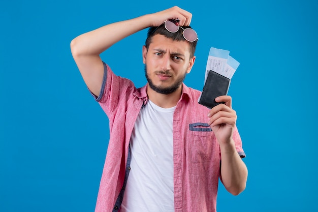 Young handsome traveler guy holding air tickets looking at camera with sad expression on face standing over blue background