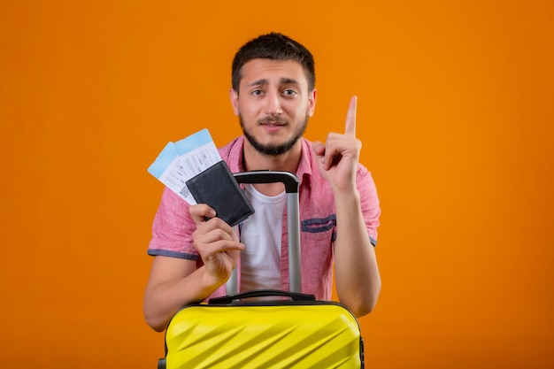 Young handsome traveler guy holding air tickets pointing up with finger reminds himself not to forget important thing standing with suitcase over orange background