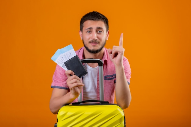 Ragazzo giovane viaggiatore bello che tiene i biglietti aerei rivolti verso l'alto con il dito ricorda a se stesso di non dimenticare cosa importante in piedi con la valigia su sfondo arancione