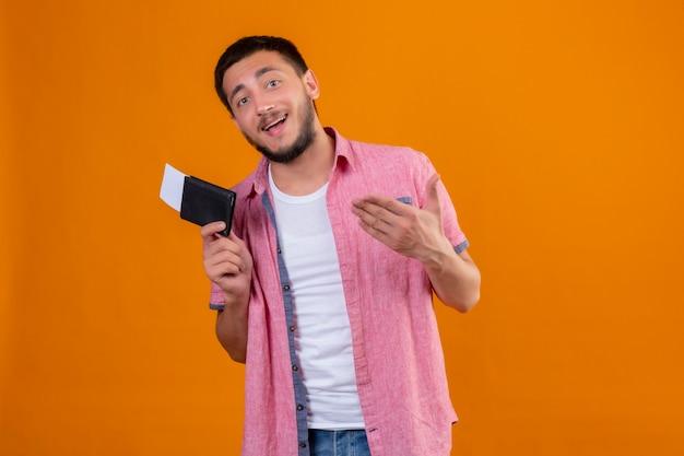Молодой красивый путешественник, держащий авиабилеты, указывая рукой на них, счастлив и позитивно смотрит в камеру, улыбаясь, стоя на оранжевом фоне