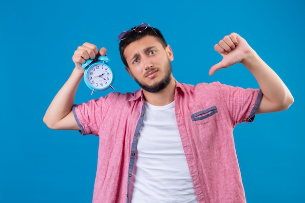 Young handsome traveler guy holding alarm clock looking at camera with sad expression on face showing thumbs down standing over blue background